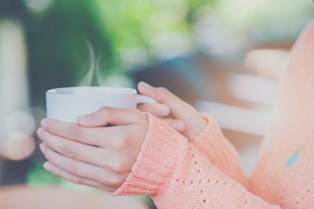 Main de femme en pull chaud tenant une tasse de café. Photo Premium