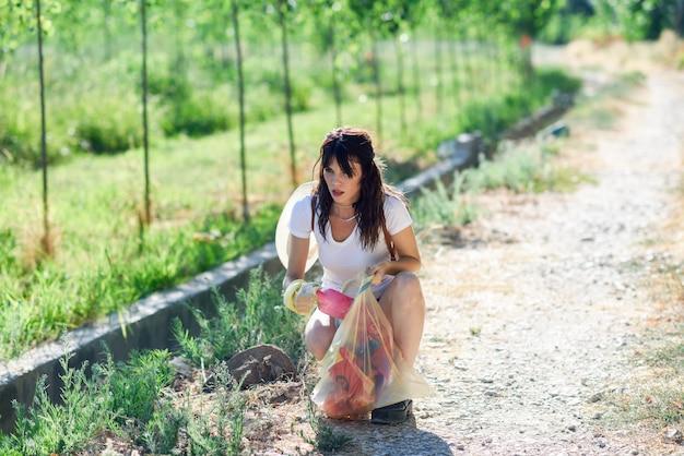Main de femme ramassant des ordures de l'herbe à la campagne Photo Premium