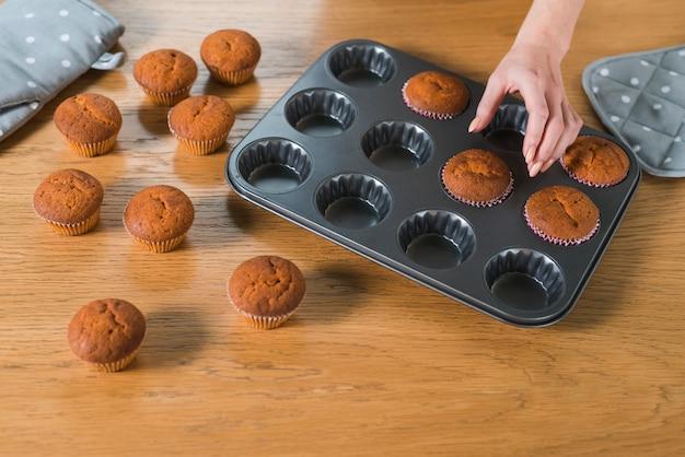 Main de femme retirant des muffins cuits du moule à cupcake sur une table en bois Photo gratuit