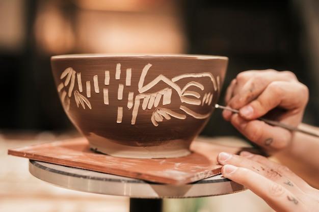 Main de femme sculpture sur le bol de peinture Photo gratuit