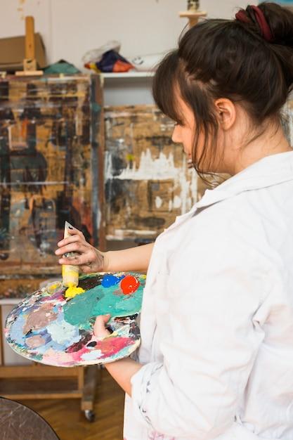 Main de femme serrant le tube de peinture jaune sur la palette de peinture en désordre Photo gratuit