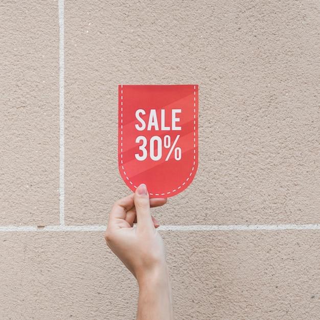 Main de femme avec signe de vente rouge Photo gratuit