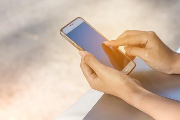 Main de femme sur smartphone avec grand écran vide et cadre moderne sans design Photo Premium