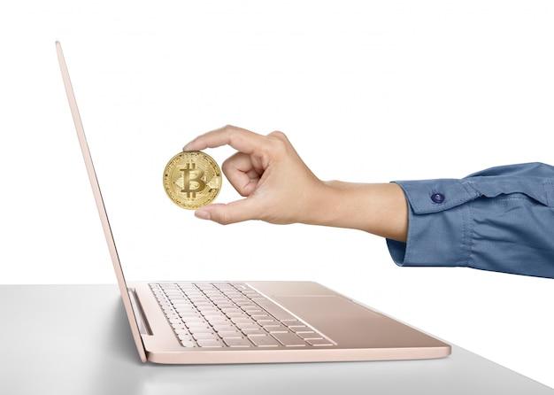 Main de femme tenant un bitcoin doré devant un ordinateur portable Photo Premium
