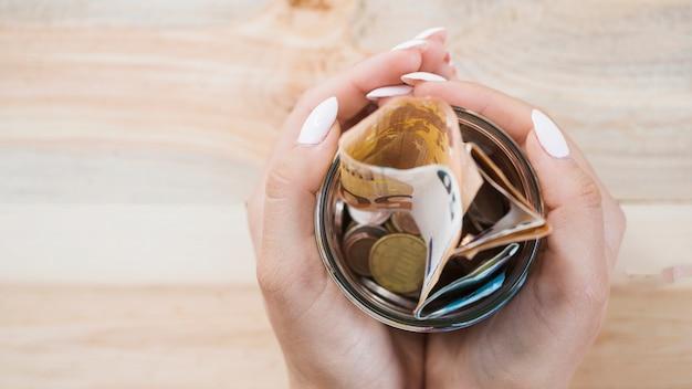 Main de femme tenant un bocal en verre avec des billets et des pièces en euros sur fond en bois Photo gratuit