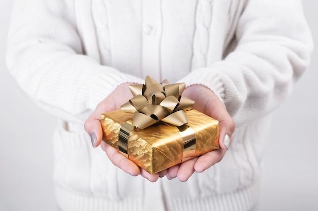 Main De Femme Tenant La Boîte-cadeau Or Sur Fond Blanc. Photo Premium