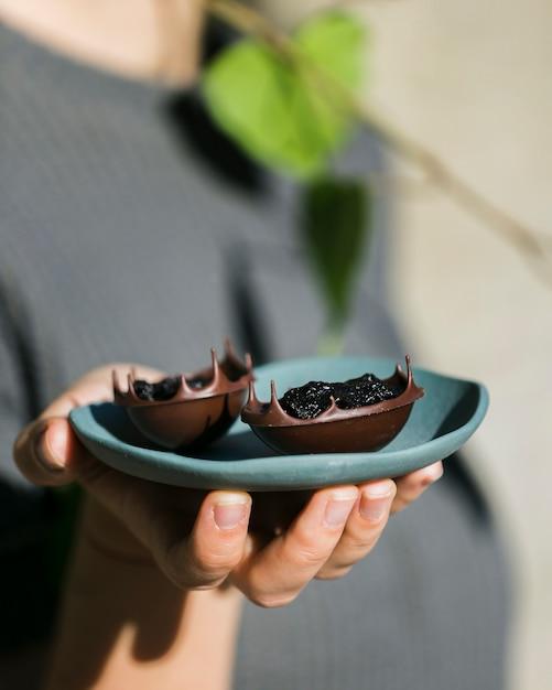 Main de femme tenant des bols à dessert savoureux dans une assiette en céramique Photo gratuit