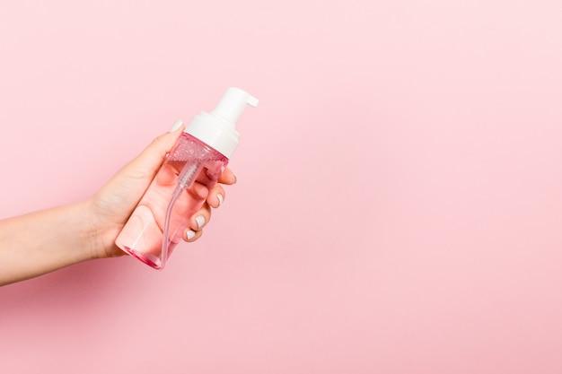 Main femme tenant une bouteille de crème de pulvérisation de lotion isolée. Photo Premium