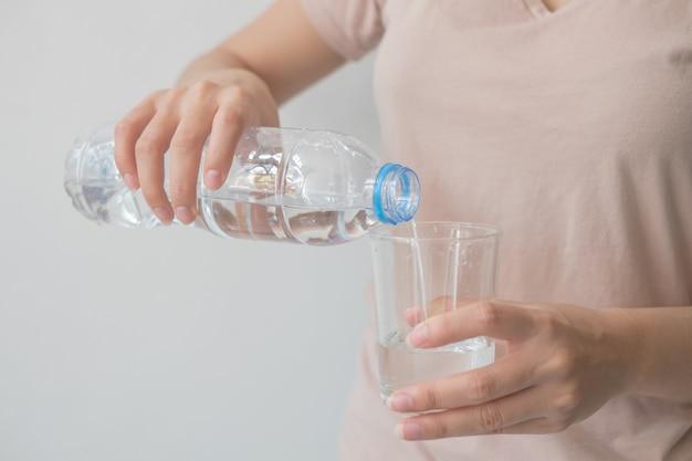 Main de femme tenant une bouteille d'eau verser de l'eau dans un verre Photo Premium