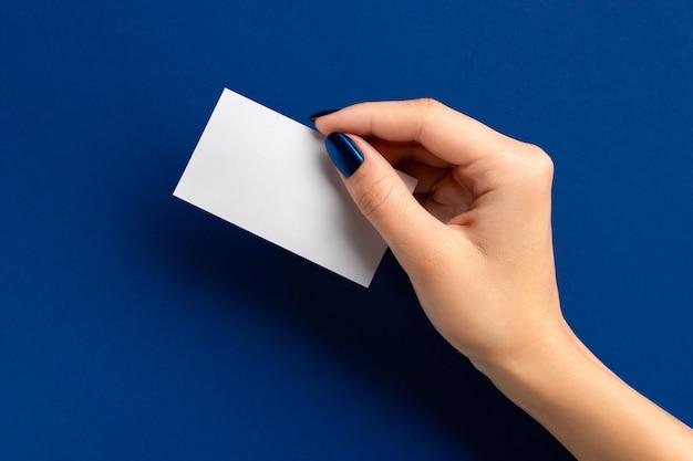 Main De Femme Tenant Une Carte Papier Sur Fond Bleu. Salon De Beauté Maquette Modèle De Carte De Voeux Photo Premium