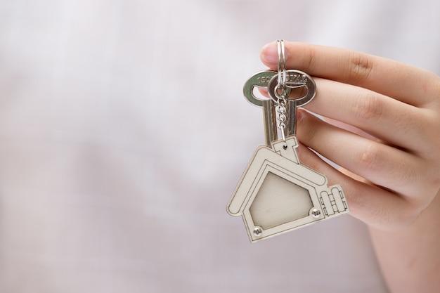 Main de femme tenant la clé de la maison. concept pour les affaires immobilières. Photo Premium