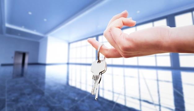 Main de femme tenant les clés d'un appartement. Photo Premium