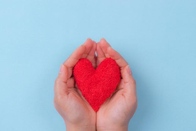 Main de femme tenant un coeur rouge. journée mondiale du coeur. Photo Premium