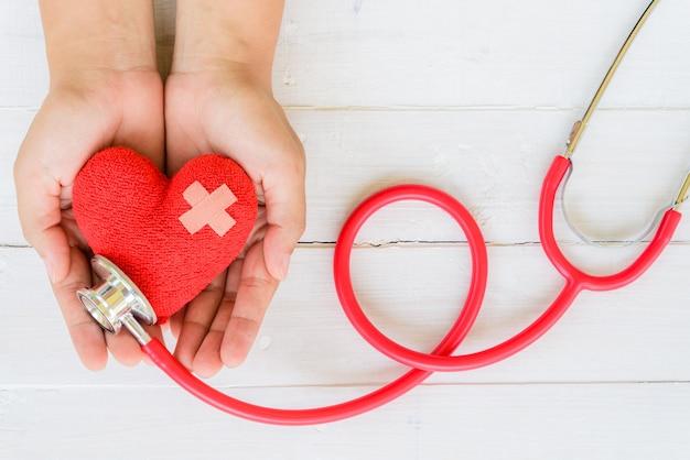Main de femme tenant un coeur rouge avec stéthoscope sur fond en bois blanc Photo Premium