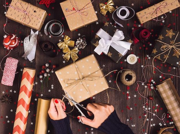 Main de femme tenant une corde de ficelle avec des ciseaux pour couper et emballer une boîte de cadeau de noël Photo gratuit