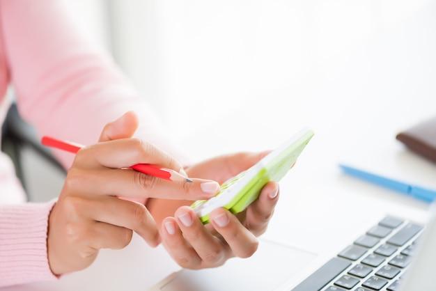 Main de femme tenant un crayon rouge et travaillant avec une calculatrice, un document commercial et un ordinateur portable co Photo Premium