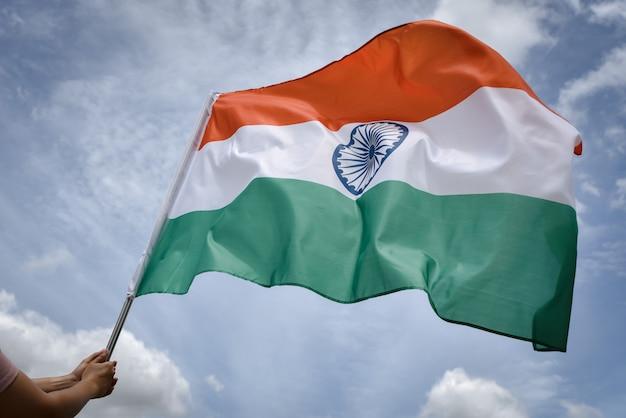 Main de femme tenant le drapeau de l'inde sur le ciel bleu Photo Premium