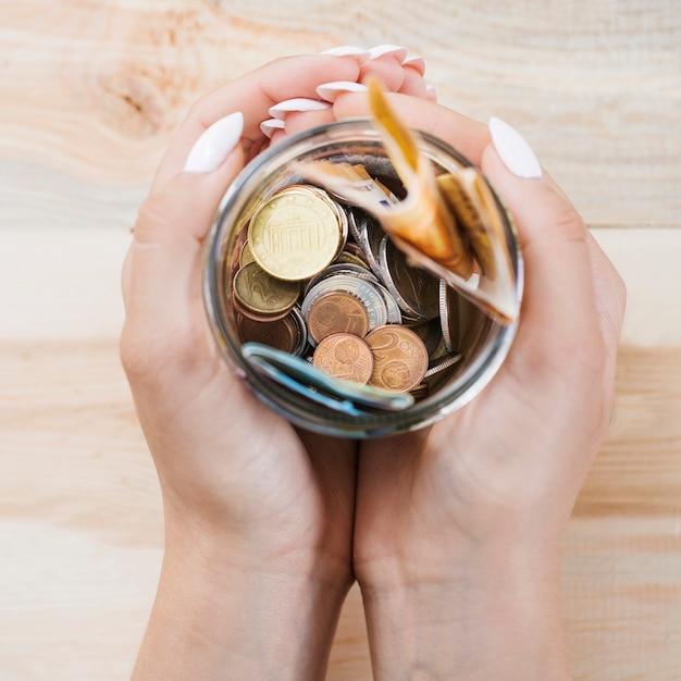 Main de femme tenant épargnant dans le pot sur fond en bois Photo gratuit
