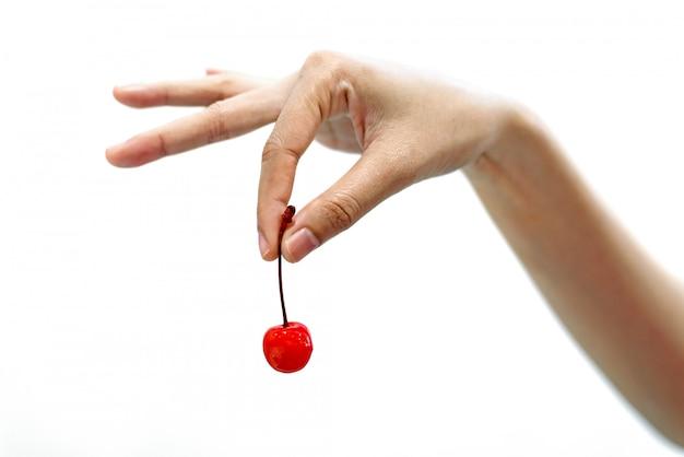 Main de femme tenant un fruit de cerises rouges isolé sur fond blanc Photo Premium