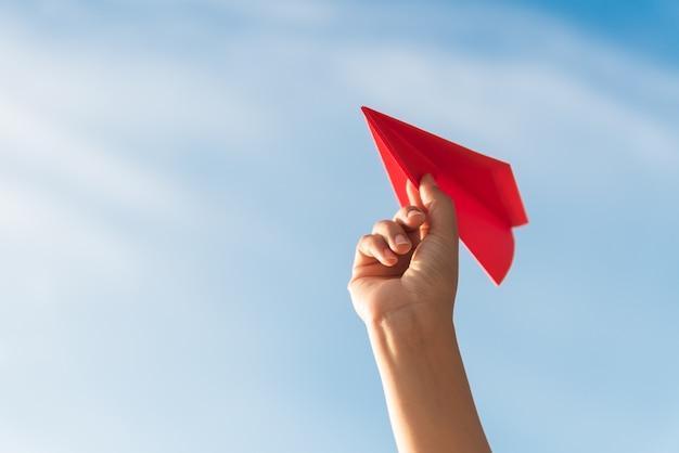 Main de femme tenant une fusée de papier rouge sur fond de ciel bleu. Photo Premium