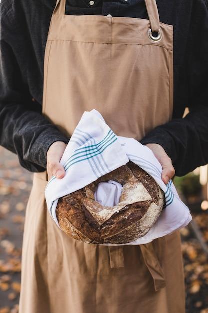 Une main de femme tenant un gros pain bagel enveloppé dans une serviette blanche Photo gratuit