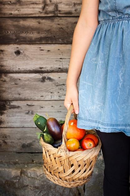 Main de femme tenant un panier rempli de légumes Photo gratuit