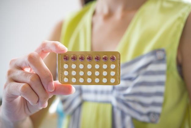 Main de femme tenant un panneau contraceptif pour prévenir la grossesse Photo gratuit