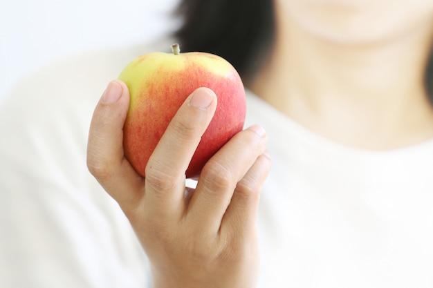 Main de femme tenant une pomme rouge. Photo Premium