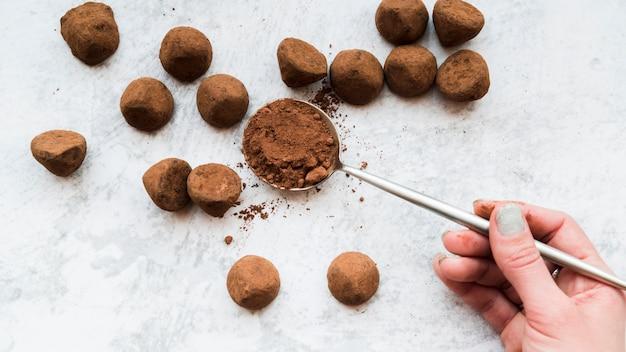 Une main de femme tenant de la poudre de cacao en cuillère sur un fond texturé blanc Photo gratuit