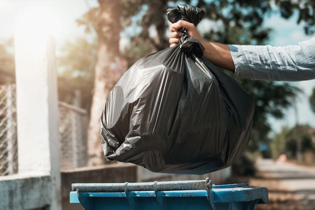 Main de femme tenant un sac poubelle noir mis à la poubelle Photo Premium