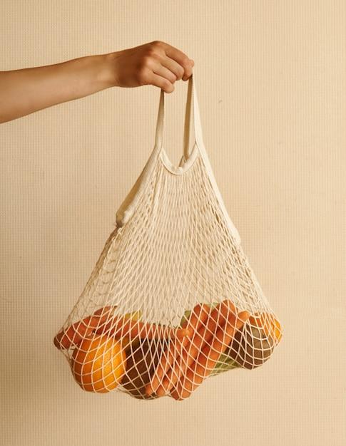 Main de femme tenant un sac shopping avec des légumes, des fruits dans des tons chauds et terreux Photo Premium