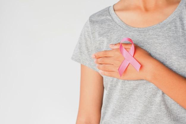 Main de femme tenant la sensibilisation au cancer du sein ruban rose. concept santé et médecine Photo Premium