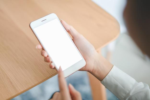 Main de femme tenant le smartphone avec un écran blanc sur la table à café. Photo Premium