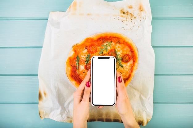 Main de femme tenant le smartphone sur la pizza Photo gratuit