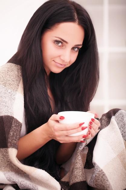 Main de femme tenant une tasse de café. avec une belle manucure d'hiver. boire, mode, matin Photo Premium