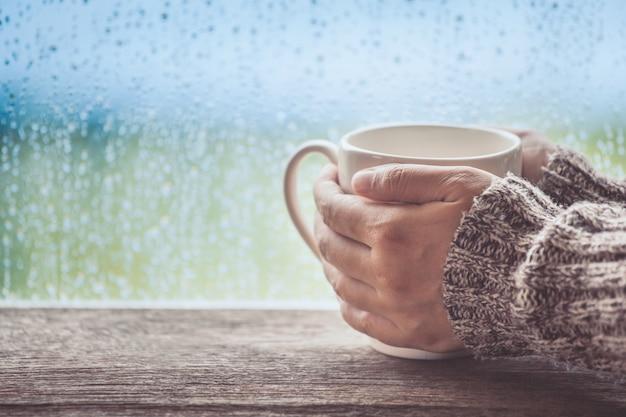 Main de femme tenant la tasse de café ou de thé sur le fond de la fenêtre de jour de pluie Photo Premium