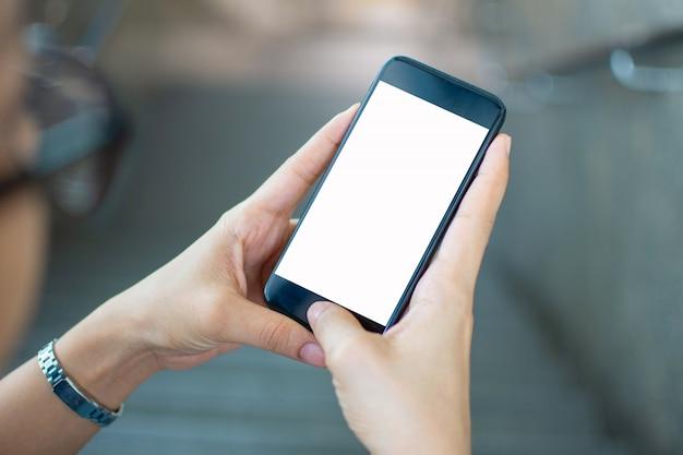Main de femme tenant un téléphone intelligent avec l'arrière-plan flou. mise au point sélective et mise au point douce. Photo Premium