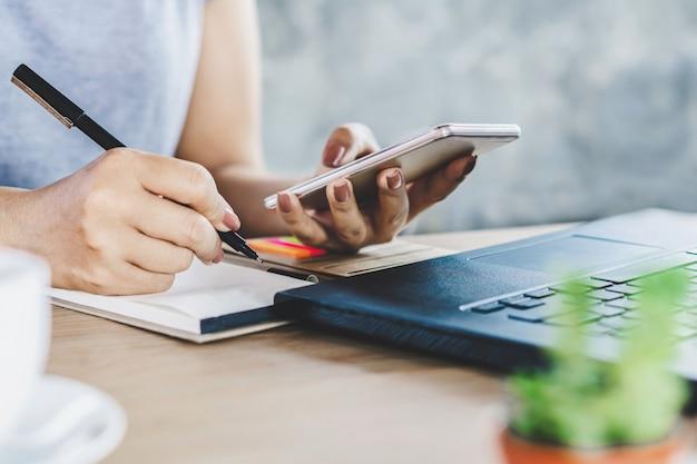 Main de femme tenant le téléphone intelligent et l'écriture Photo Premium