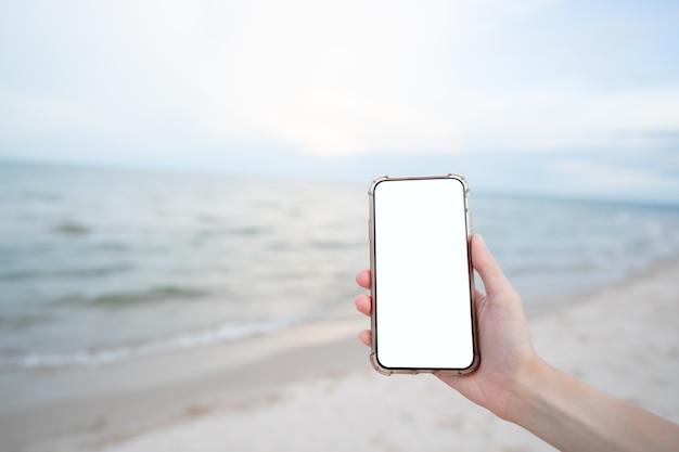Main De Femme Tenant Un Téléphone Mobile Avec Une Maquette D'écran Blanc Vierge Sur La Plage. Photo Premium