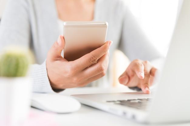 Main de femme tenant un téléphone portable blanc sur une table avec un ordinateur portable au bureau Photo Premium
