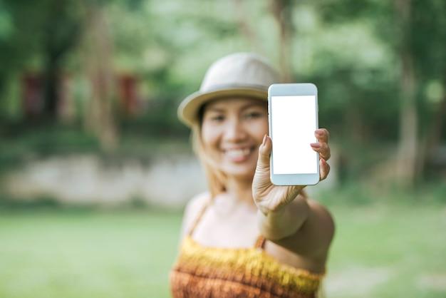 Main de femme tenant le téléphone portable, smartphone avec écran blanc Photo gratuit