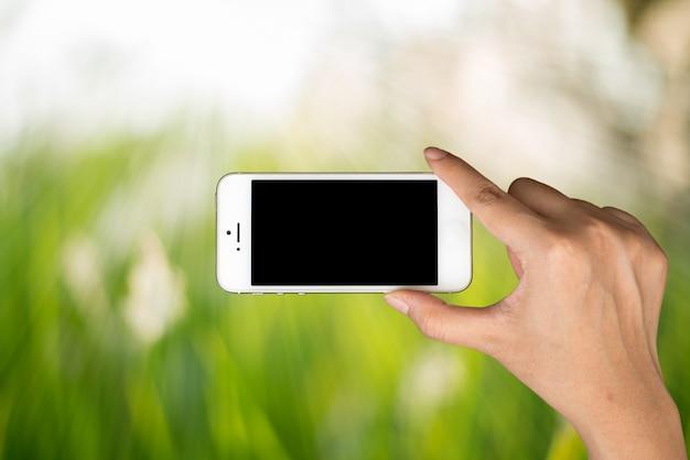 Main de femme tenir et téléphone intelligent sur la lumière du jour avec fond de nature floue verte. Photo gratuit