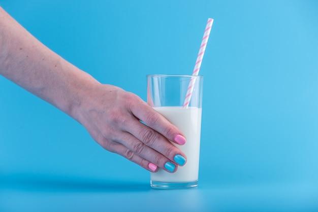 Main de femme tient un verre de lait frais avec une paille sur un fond bleu. concept de produits laitiers sains contenant du calcium Photo Premium