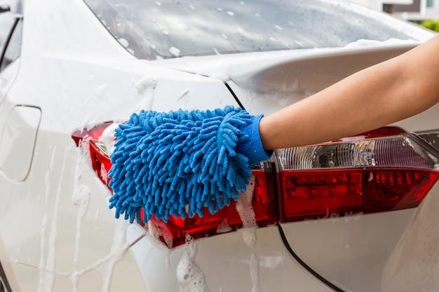 Main de femme avec tissu en microfibre bleu, lavage de voiture de feu arrière moderne ou automobile de nettoyage. Photo Premium