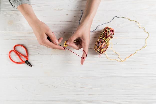 Main femme tricotant avec de la laine colorée sur une table en bois Photo gratuit