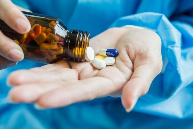 Une main de femme verse les pilules de la bouteille Photo gratuit