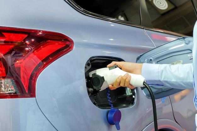 Main de femmes alimentant un véhicule neuf via une machine à l'électricité rechargeable Photo Premium