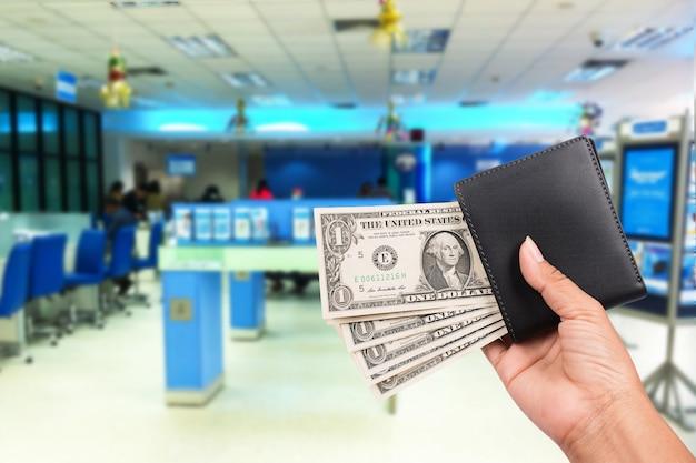 Main les femmes détiennent de l'argent dans un portefeuille noir sur le fond de la banque Photo Premium