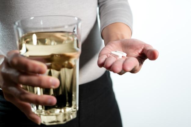 Main de femmes tenant la médecine avec le verre du concept de récupération de médecine de l'eau Photo Premium
