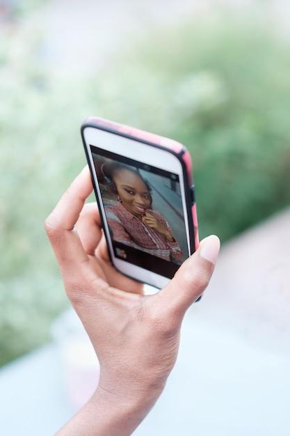 Main De Fille Afro Noire Tenant Le Smartphone Et Faisant Selfie Photo Premium